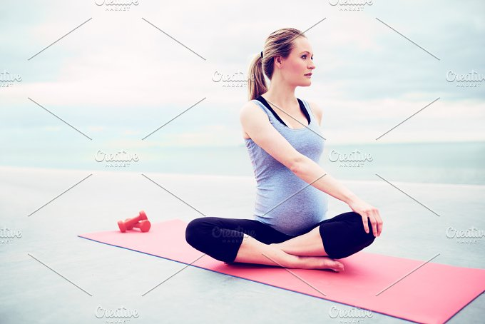 Pregnant young woman doing fitness exercises.jpg - People