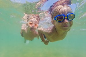 Two boys dive in swimming goggles in