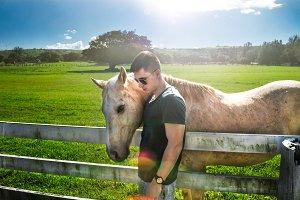 Man hug white horse on rancho