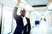 Businessman in a Subway Train Holding on Railing.jpg