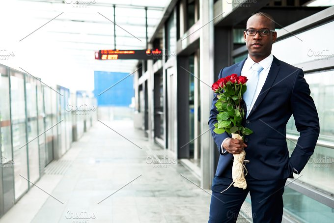 Businessman at Metro Holding Bouquet of Flowers.jpg - People