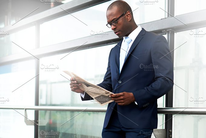 Businessman Reading Newspaper at the Walkway Side.jpg - Business