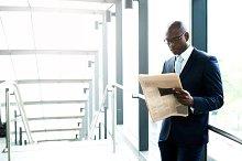Businessman Reading a Newspaper Inside a Building.jpg