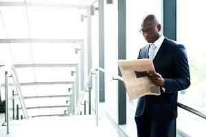 Businessman Reading a Newspaper Inside a Building.jpg