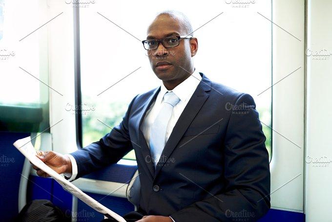 Businessman with Newspaper Inside a Train.jpg - Business