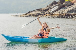 Mother and son kayaking at tropical
