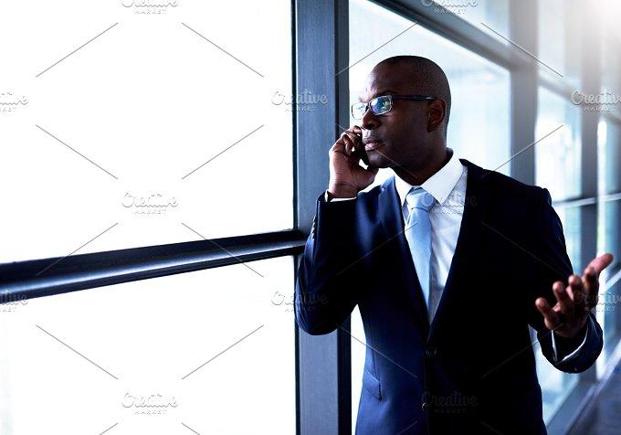 Businessman Talking on Phone Inside the Building.jpg - Business