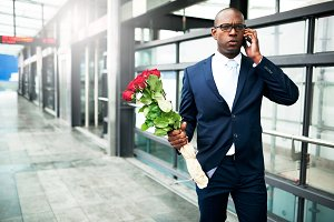Businessman with Flowers Calling on his Phone.jpg