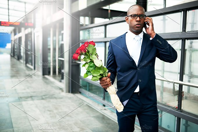 Businessman with Flowers Calling on his Phone.jpg - People