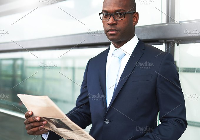 Businessman with Newspaper Looking at Camera.jpg - Business