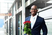 Happy Businessman Waiting at the Metro with Roses.jpg