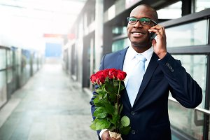 Happy Businessman with Flowers Calling on Phone.jpg