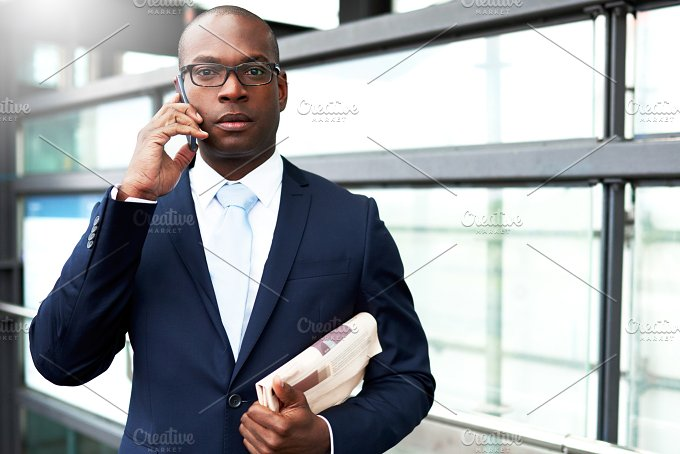 Young Businessman on Phone Looking at Camera.jpg - Business