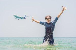 A man bathes in the sea, an airplane
