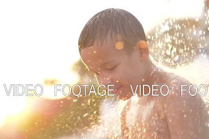 Child taking beach shower at sunset