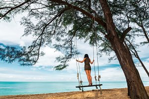 Woman on a swing by the sea