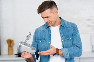 confused adult man holding mixer in