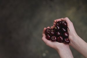 Hands Holding Cherries in a Heart