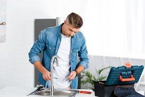 handsome adult man repairing faucet
