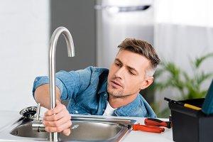 handsome man repairing faucet of kit