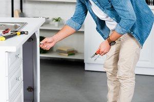 handsome man fixing kitchen sink wit