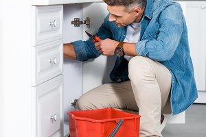 handsome adult man repairing kitchen