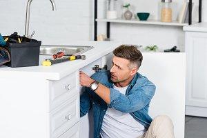 handsome man repairing kitchen sink
