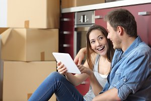 Couple moving home checking tablet o