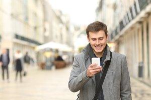 Happy man walking checking smart pho