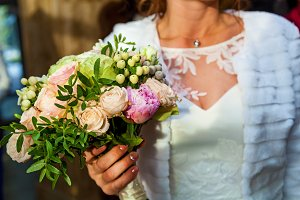 bride holds a wedding bouquet of ros