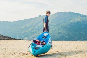Young man carrying his kayak along