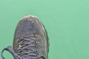 Hiking boot hanging above water