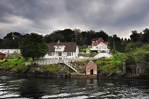 Wooden house at the fjord coast