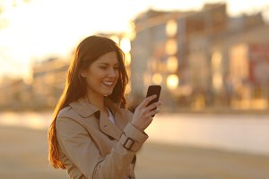Woman using a smart phone at sunset