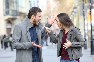 Angry couple arguing in the street