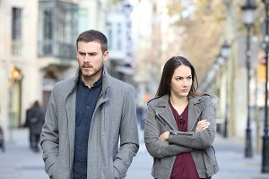 Angry couple walking in the street a