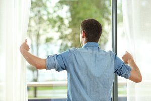 Back view of man opening curtains an