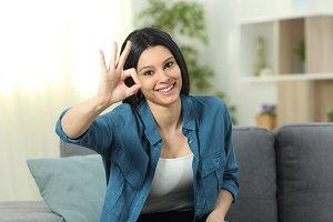 Happy woman gesturing ok sign at hom