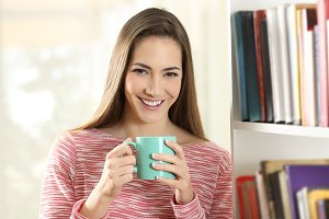 Happy woman holding a coffee cup loo
