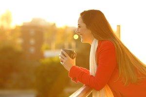 Happy woman in a balcony looks away