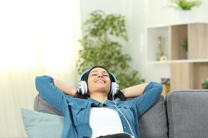 Happy woman relaxing at home listeni