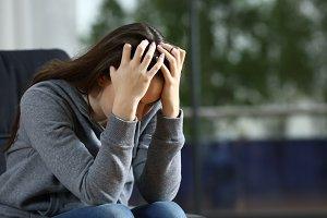 Sad woman complaining alone on a cou