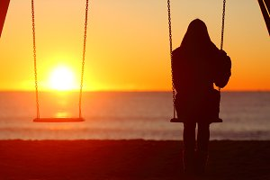 Single woman sitting on a swing cont