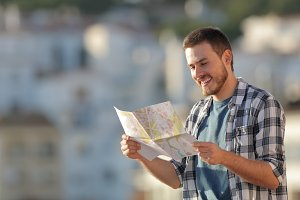Happy tourist checking paper map in