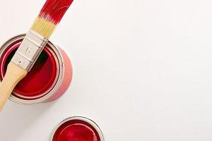 Paintbrush on red paint pot on white