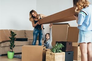 Family with cardboard boxes in new