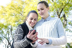 Two women using a cell phone