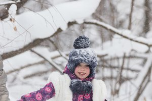 Winter forest. Smiling little girl