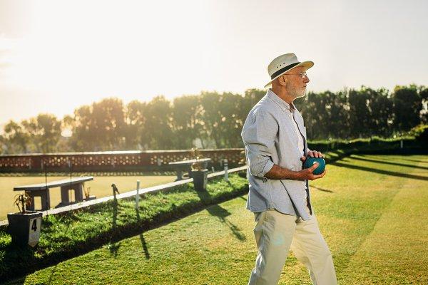 Elderly man standing in a lawn