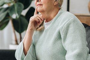 pensive senior woman sitting on sofa